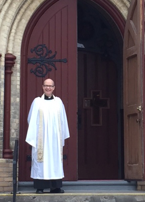 Father Rob Ross at the doors of the church